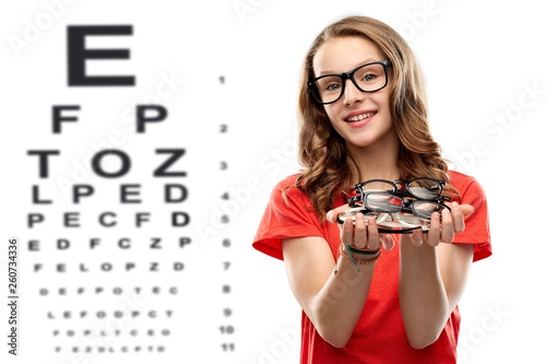 Fotografía  vision, eyesight and eyewear concept - smiling teenage student girl holding pile