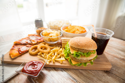 fast food and unhealthy eating concept - close up of double hamburger or cheeseburger, deep-fried squid rings, french fries, pizza and cola drink on wooden board © Syda Productions