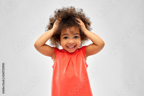 Fototapeta  childhood and people concept - overwhelmed little african american girl holding