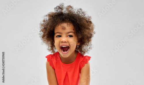 emotion, childhood and expression concept - happy laughing little african americ Fototapeta