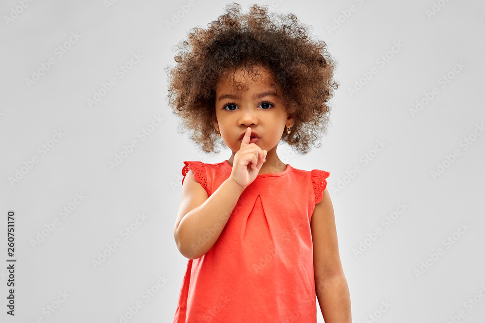 Fototapeta childhood and people concept - little african american girl making shush gesture over grey background