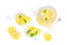 Homemade Lemonade In Glasses And A Jar, With Fresh Lemons, Mint, And Ice Cubes, Shot From The Top On A White Background With Copy Space