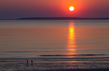Couple Walking On Quite And Empty Beach At Sunset  On The West Coast Of Ireland
