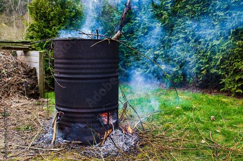Obraz na plátně A burning fire of garden waste in an old rusty barrel