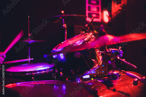 Fotografiet  Drummer with a drumsticks in his hands playing on drum set on stage on the black background