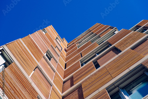 View from the floor of the facade of a modern building clad in ecological wood over clean blue sky, concept of sustainable construction background, copy space.