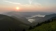 Peaceful evening sunset over green alpine mountains nature with mist clouds in valley Time lapse
