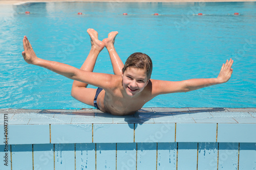 Smiling boy lying on the edge of blue pool