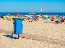 Crowded Beach With Garbage Bin