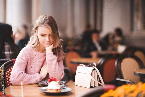 Photographie  Blonde teen girl 16-17 year old sitting in cafe eating cake outdoors
