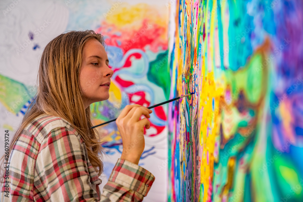 Fototapeta Joyful young female artist painting on the wall, using brush and bright acrylic paints