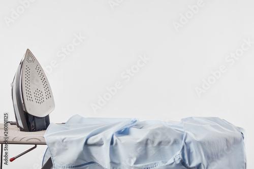 Iron and blue shirt on ironing board isolated on white