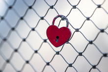 Red Heart Shaped Keylock On A Fence