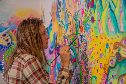 Foto Concentrated young woman coloring her bedroom wall in psychedelic mind flow styl