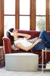 Pretty young woman listening to music while relaxing on couch at home.