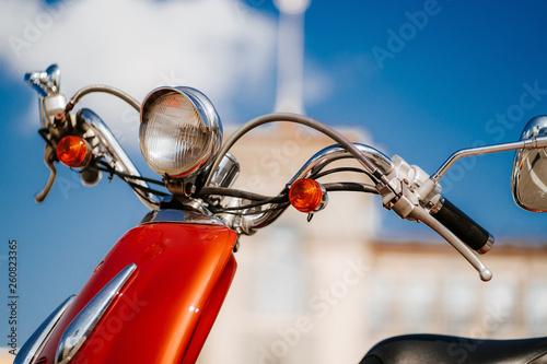 Fotografiet  Closeup chrome detail and headlamp of orange retro vintage scooter under blue sk