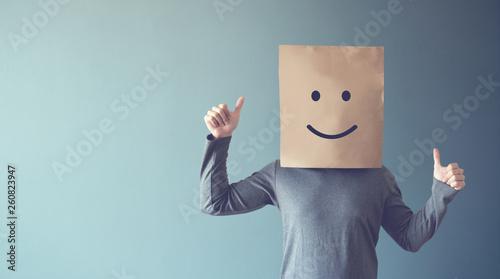 Fotografía  Man covering his face with a smiling face emoticon, copy space.