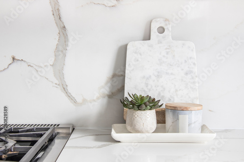 Fototapeta A beautiful closeup of a custom designed kitchen, with marble looking quartz countertop and backsplash obraz