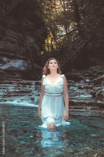 sale retailer 0f1b9 697d7 Beautiful young girl in white dress with long hair posing in Sunny mountain  gorge.