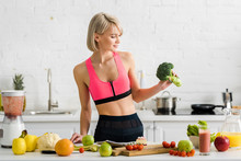Attractive Blonde Girl In Sportswear Holding Green Broccoli In Kitchen