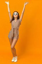 Fun, Joy And Happiness Concept. Beautiful Glamorous Stylish Young Female In White Sneakers, Striped Jumpsuit And Round Shades Rejoicing At Good Hot Summer Weather, Raising Hands And Smiling Happily
