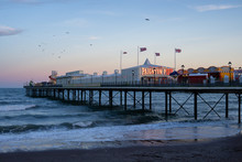 A View Of Paignton Pier, Devon From The Beach With The Waves Beneath At Sunset. Shot In Torbay.