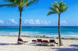 Beach chairs on the white sand on the shore of a beautiful tropi