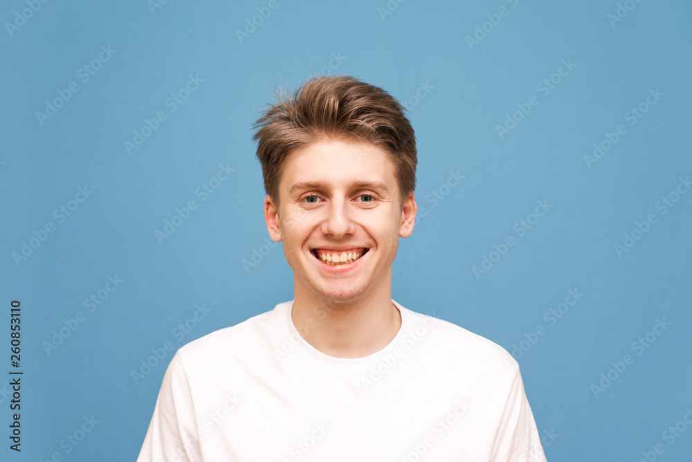 Fototapeta Smiling young man in a white T-shirt smiles and looks at the camera, a close portrait on a blue background. Happy guy is isolated on blue.