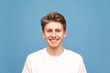 Leinwandbild Motiv Smiling young man in a white T-shirt smiles and looks at the camera, a close portrait on a blue background. Happy guy is isolated on blue.