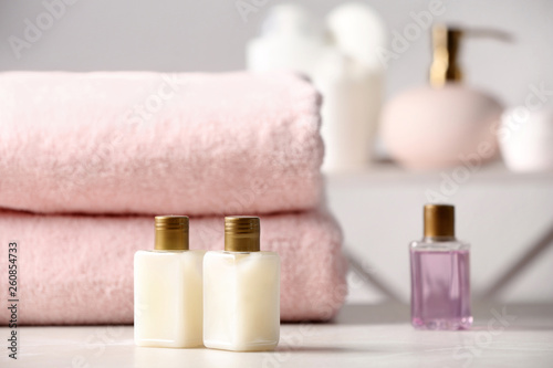 Photo Mini bottles with cosmetic products and towels on table in bathroom, space for text