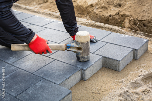 Hands of worker installing concrete paver blocks with rubber hammer Fotobehang