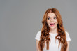 happy redhead girl looking away isolated on grey with copy space