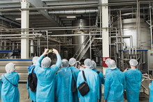 Excursion At The Factory. People In Protection, Shoe Covers, Blue Overalls Stand And Listen To A Tour Of The Metal Brewery. People Photograph Production On The Phone