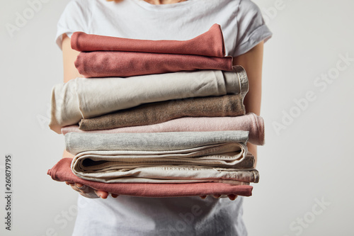 Fotografie, Obraz  Cropped view of woman holding folded ironed clothes isolated on grey