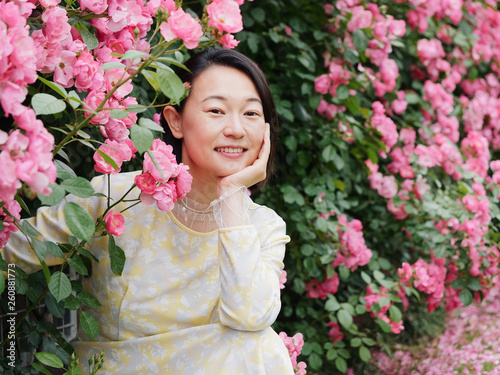 Fotografia  Outdoor portrait of beautiful middle aged Chinese woman in yellow dress smiling among pink rose flowers wall in spring garden, happy mature woman enjoy her leisure time