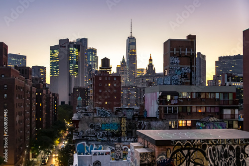 The colorful lights of the NYC skyline shine as evening falls on the buildings and streets of Manhattan