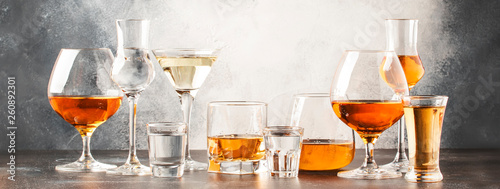 Poster de jardin Bar Set of hard strong alcoholic drinks and spirits in glasses in assortment: vodka, cognac, tequila, brandy and whiskey, grappa, liqueur, vermouth, tincture, rum. Gray bar counter background
