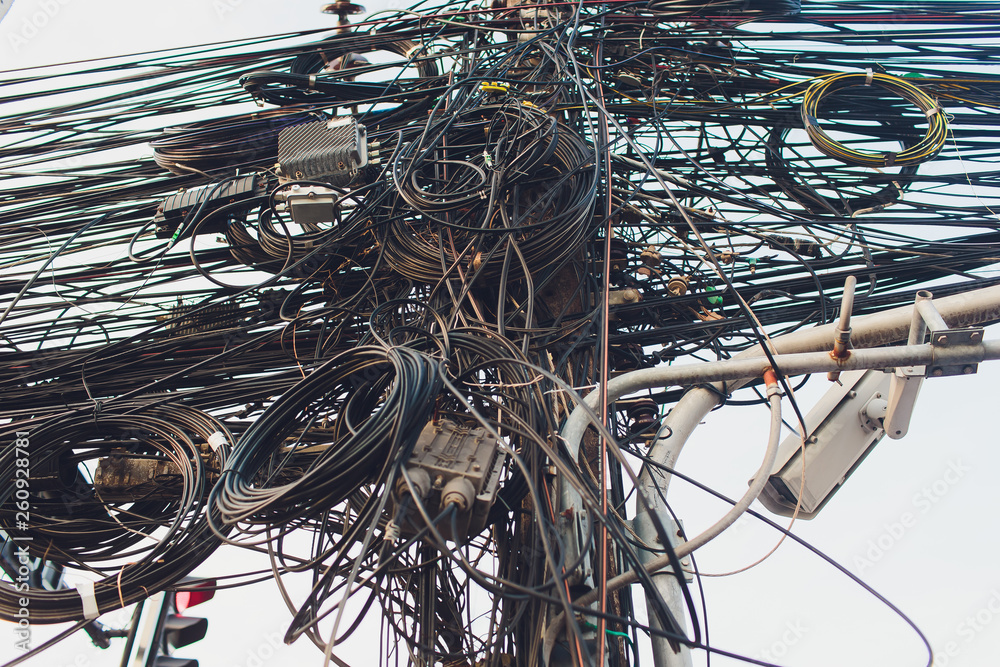 Fototapeta Crazy messy chaos wires cables on Electric poles.