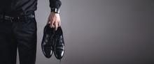 Man Holding Black Shoes. Fashi...