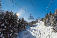 Traveling Up An Alpine Mountainside On Ski Chair Lift