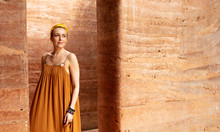 Portrait Of Beautiful Caucasian Woman Standing By The Rammed Earth Walls.