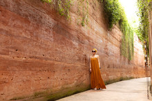 Portrait Of Beautiful Woman In Summer Dress Standing By The Rammed Earth Wall At The Park.