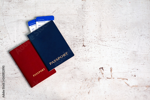 Fotografía  Two travelers passports red and blue with boarding passes for the plane