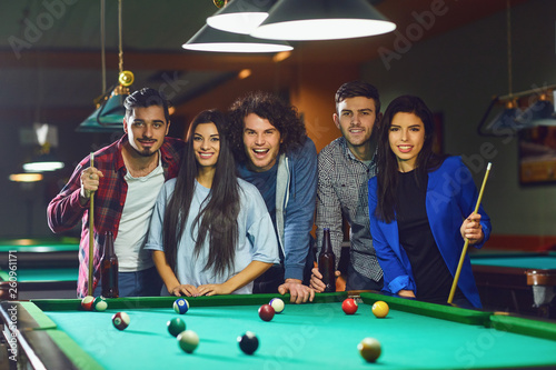 A group of young people playing fun billiards. Wallpaper Mural