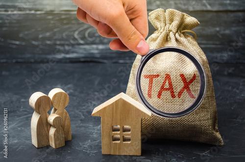 Εκτύπωση καμβά A bag with the word Tax and family stand near the house