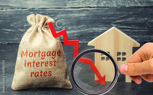 Fotografía Bag with the money and the word Mortgage interest rates and arrow to down and house