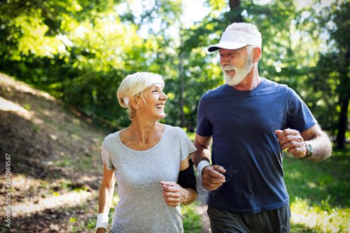 Fototapeta Fitness, sport, people, exercising and lifestyle concept - senior couple running obraz