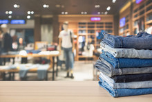 Blue Denim Jeans Stack On Wood Table Top With Abstract Blur Clothing Store In Modern Shopping Mall Defocused Bokeh Light Background