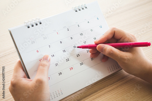 Fotomural Hand with pen writing on calendar page closeup
