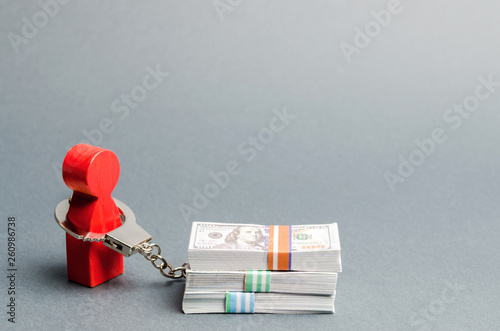 Photo A red man is handcuffed to a money